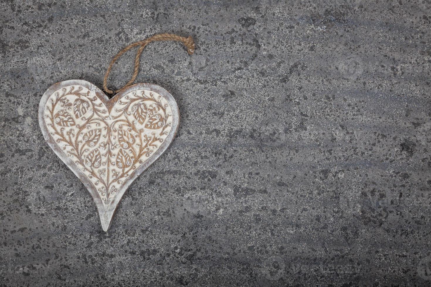 coração de madeira esculpido em fundo de pedra cinza foto