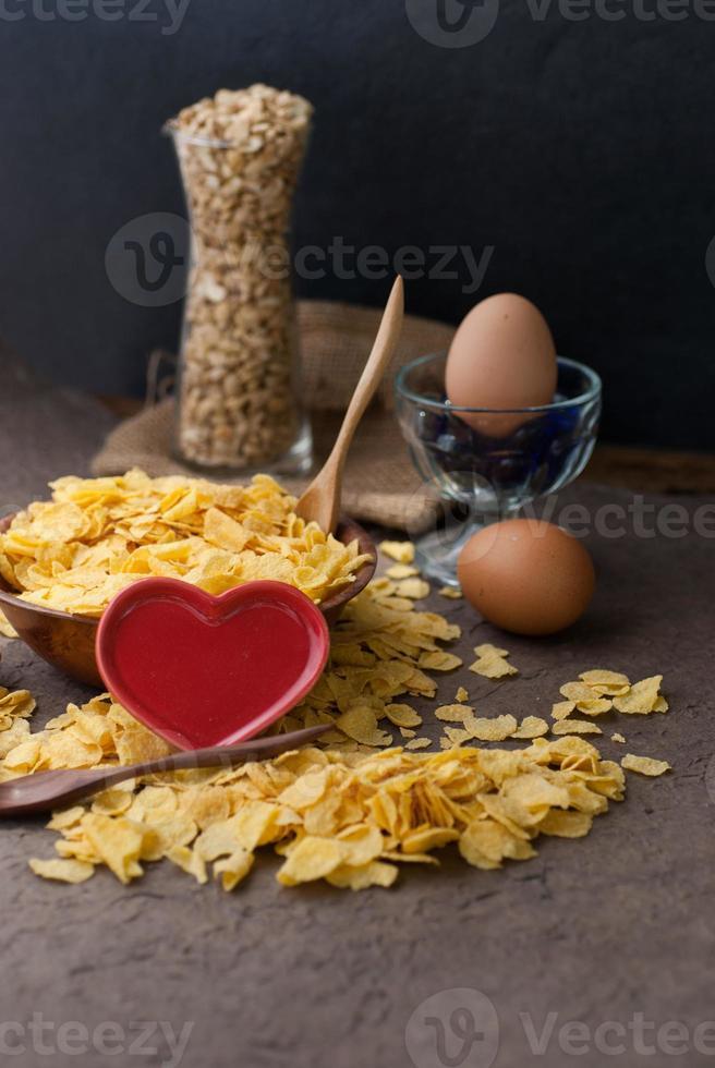 Flocons de maïs dans un bol en bois avec cuillères et coeur rouge photo