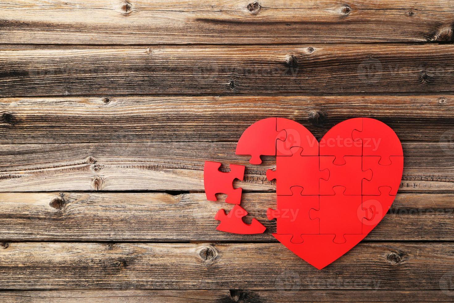 Corazón de rompecabezas rojo sobre fondo de madera marrón foto