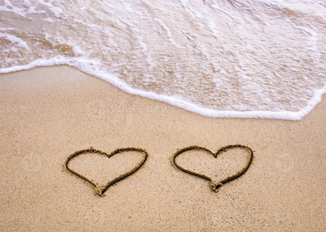 symbolen van twee harten getekend op zand, liefde concept foto