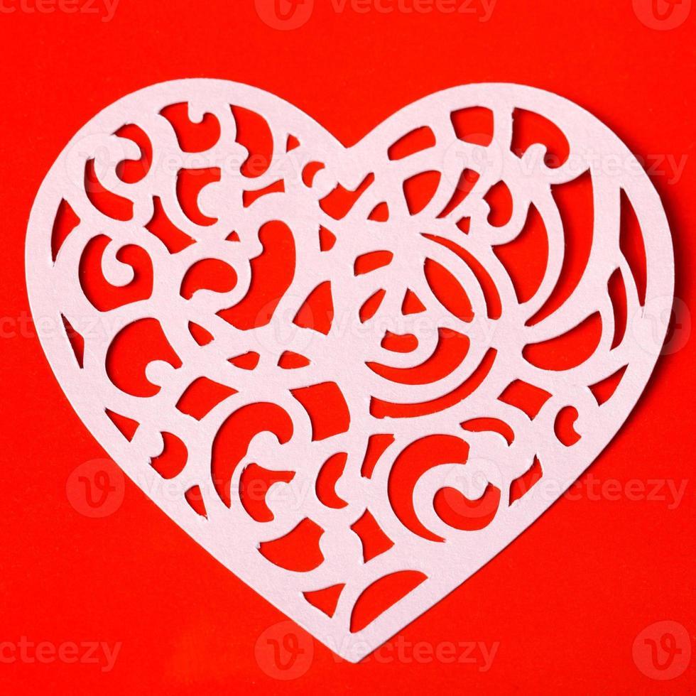 San Valentín corazón tallado en el fondo de papel rojo foto