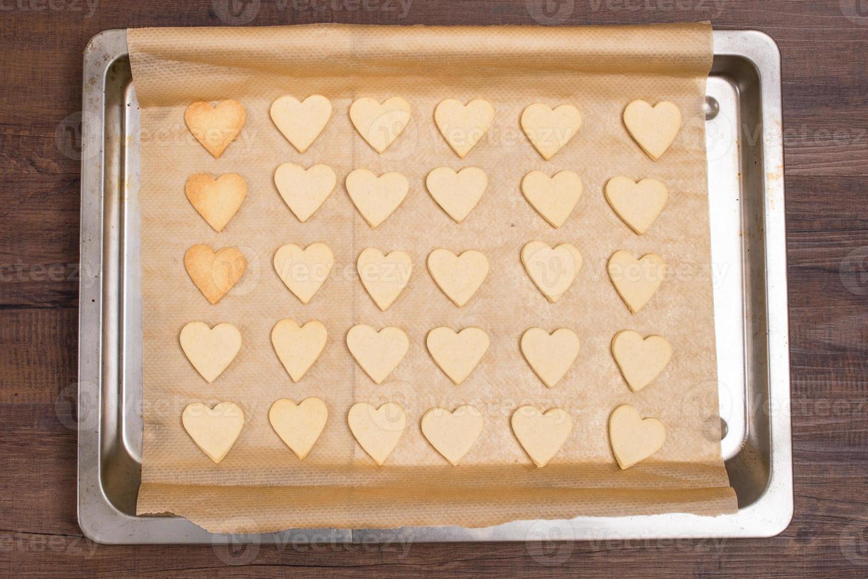 Baking sheet with heart shape cookies photo