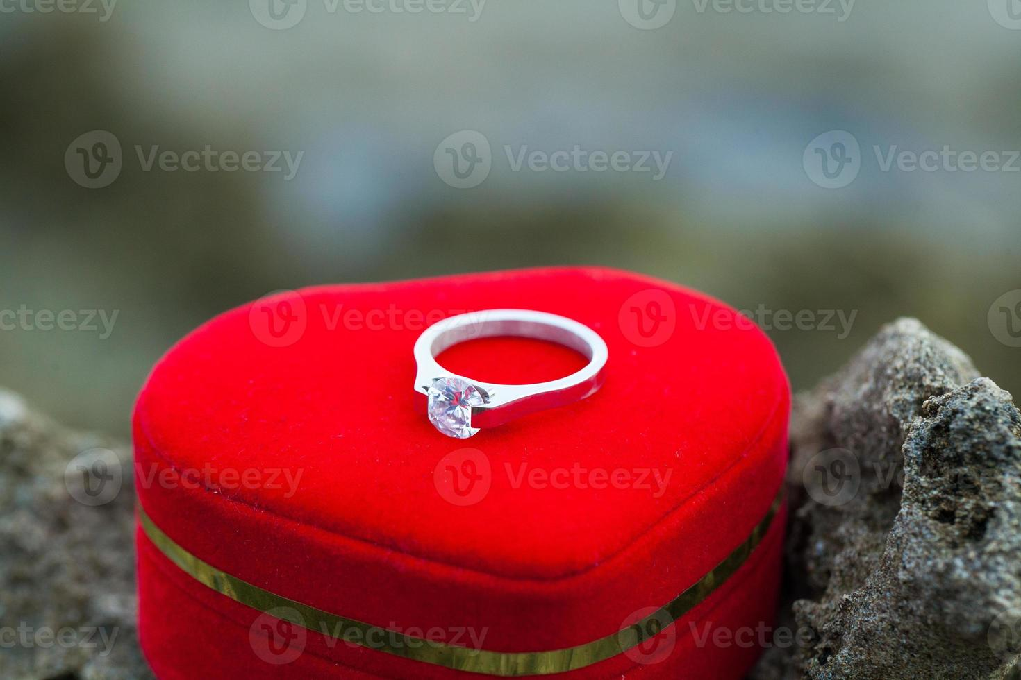 Wedding ring with heart shape symbol on beach rock photo