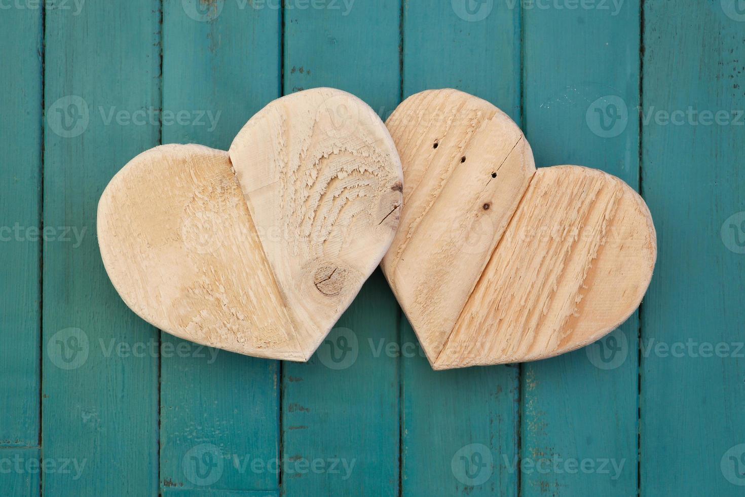 Amor corazones de madera de San Valentín sobre fondo pintado de color turquesa foto