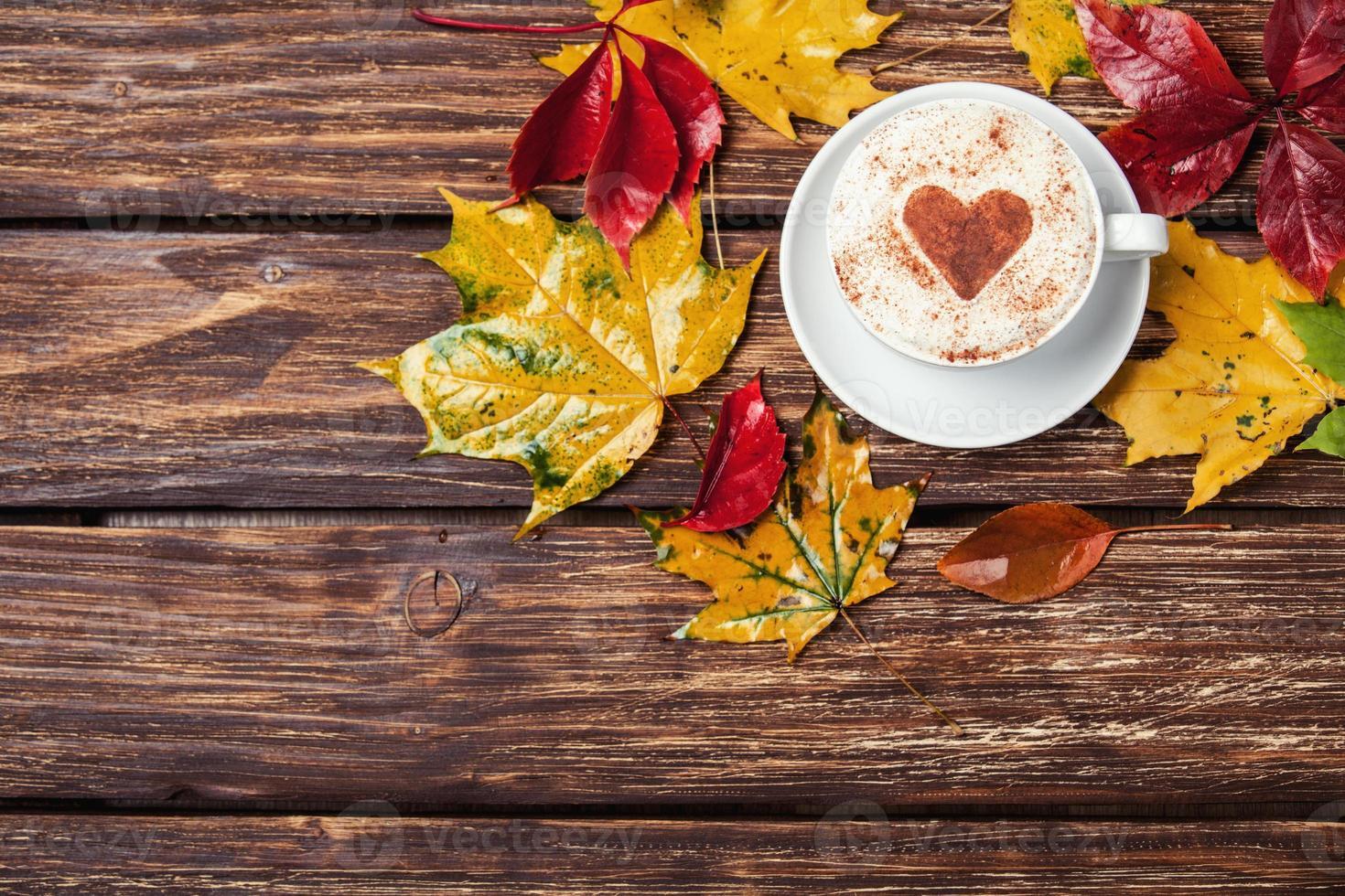 hojas de otoño y taza de café en la mesa de madera. foto