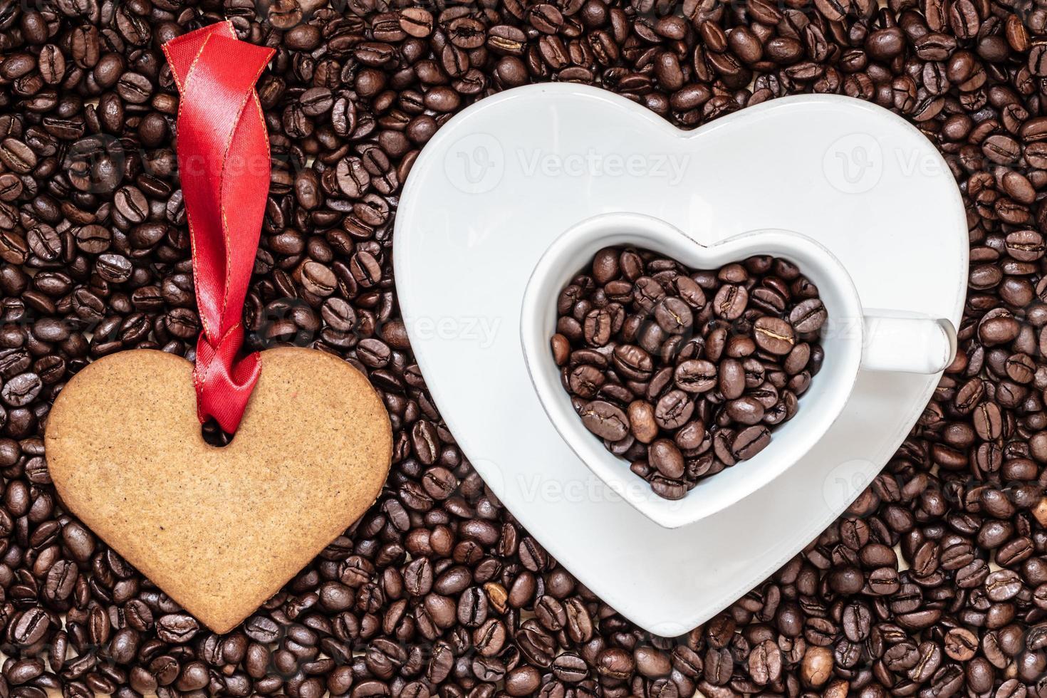 Taza en forma de corazón y galletas sobre fondo de granos de café foto