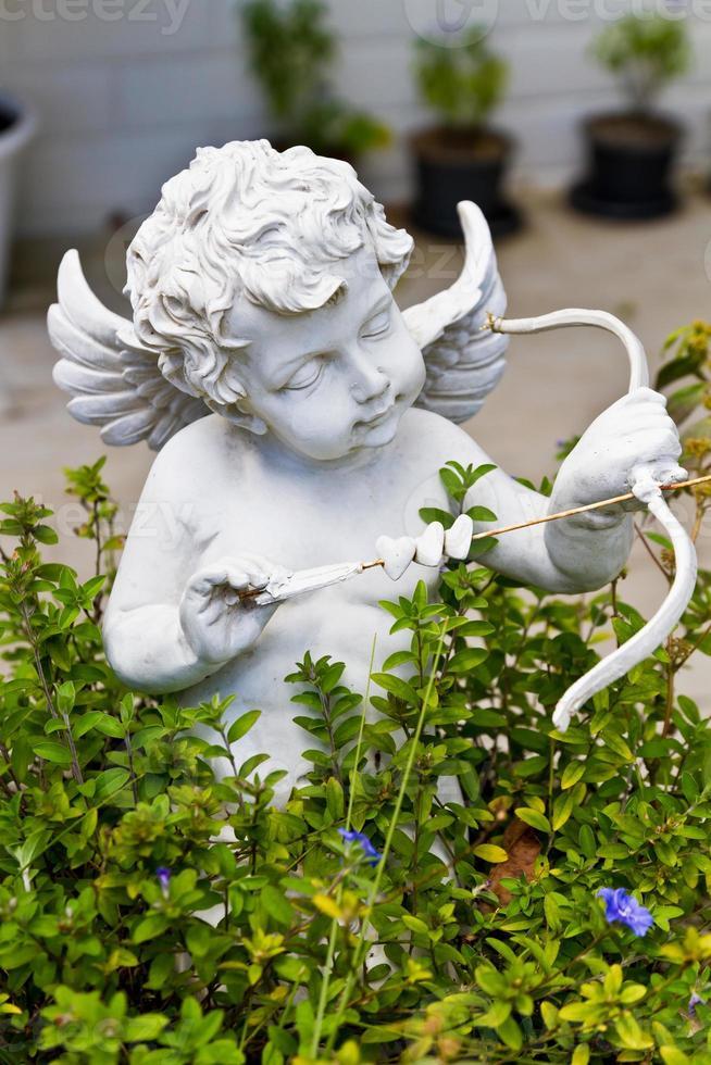 Statue of Cupid in garden. photo
