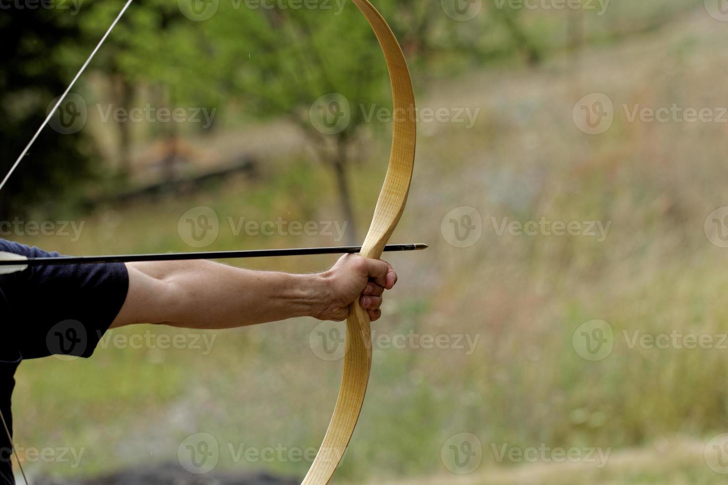 hombre disparando con arco foto