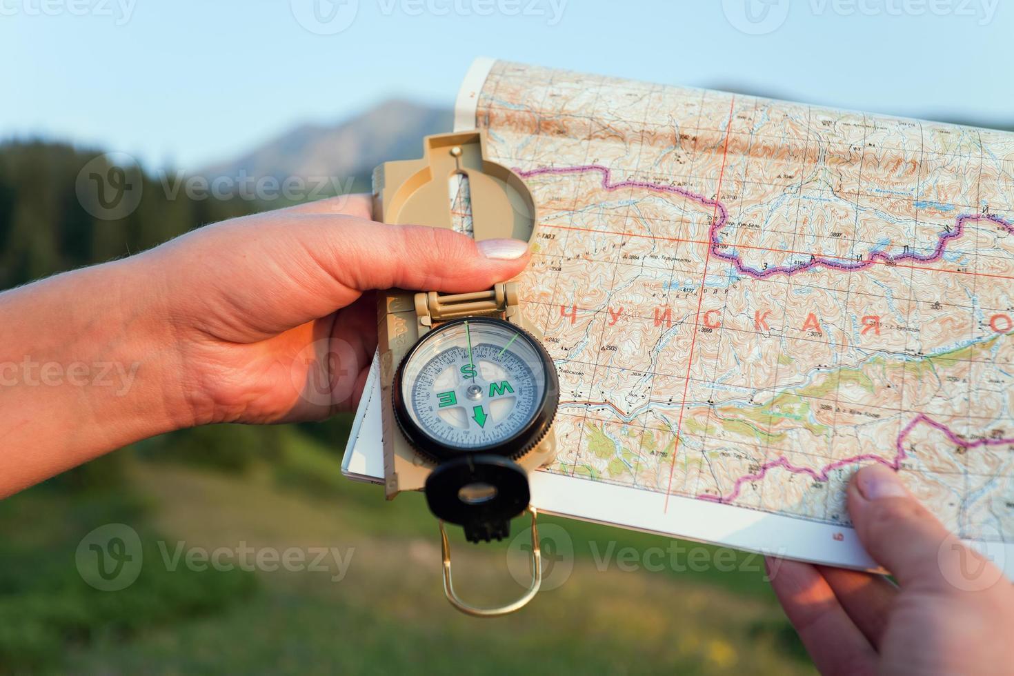Mano de turista con mapa y brújula en las montañas de Suiza foto