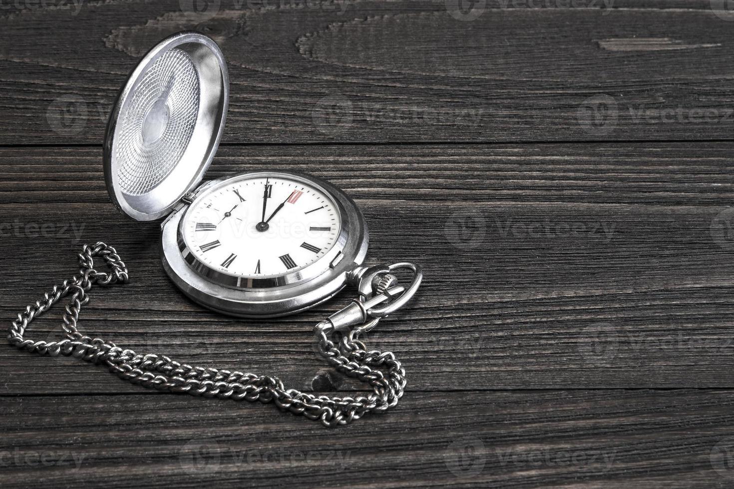 Antiguo reloj de bolsillo con cadena sobre una mesa de madera. foto