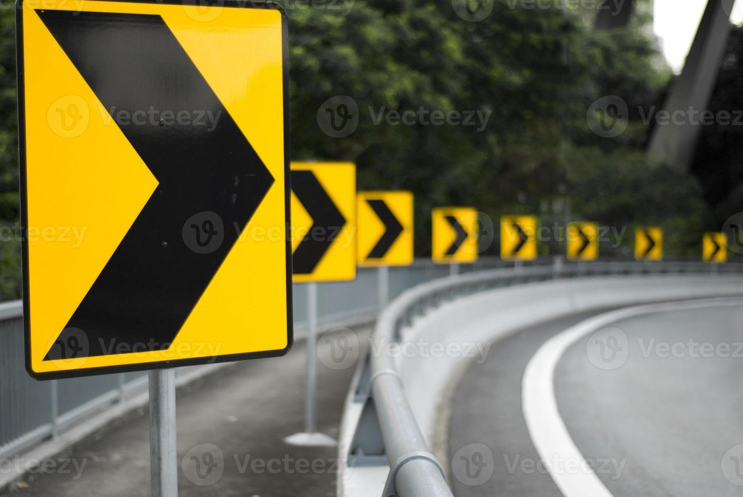 foto de letreros amarillos en la carretera apuntando hacia la derecha