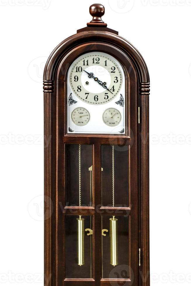 Reloj antiguo con decoración de madera tallada, aislado sobre fondo blanco. foto