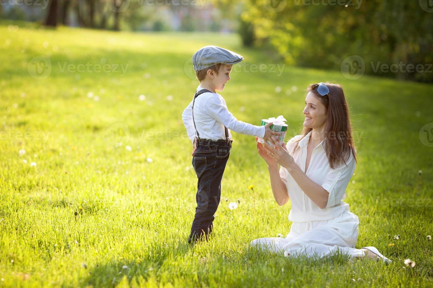 hermoso niño y mamá en el parque de primavera, flor y presente foto