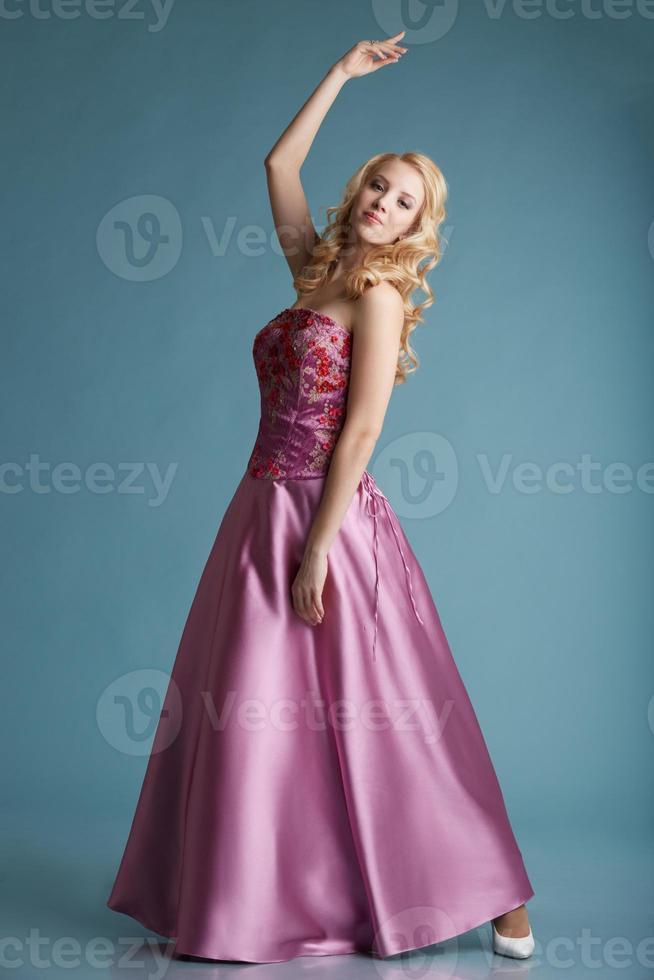Bonita chica rubia posando en vestido para el baile de graduación foto