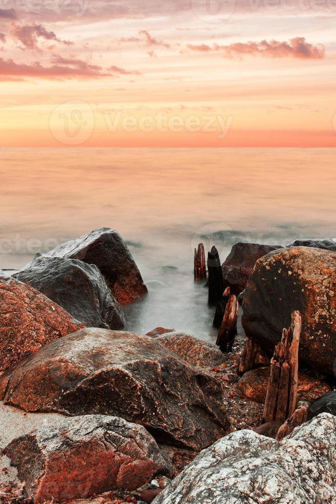 roca, agua y puesta de sol foto