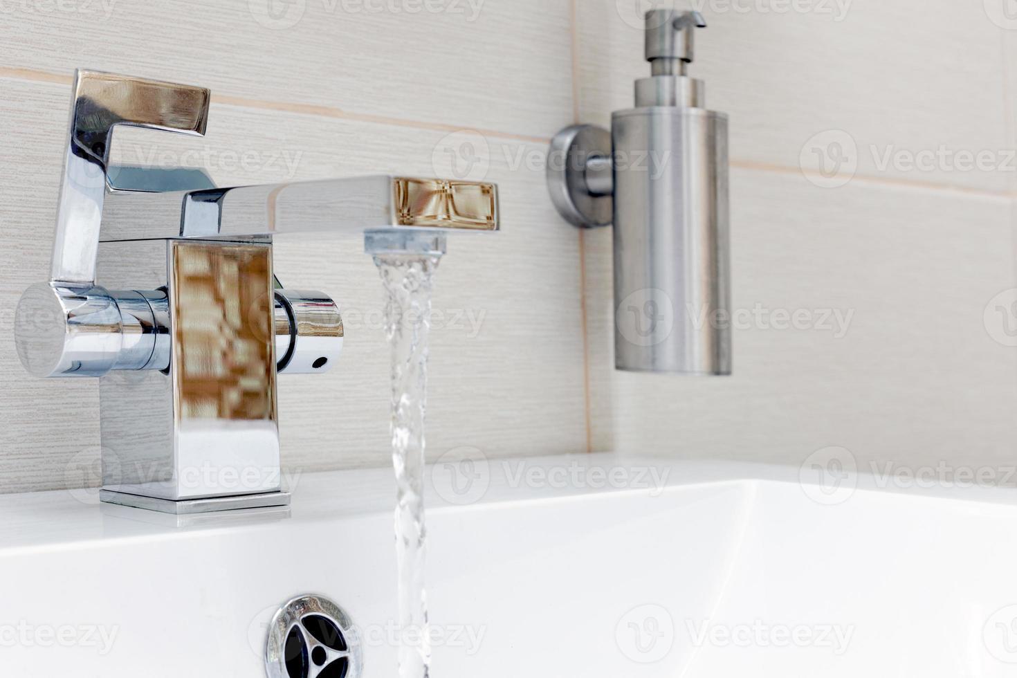 grifo de placa de cromo con agua. foto