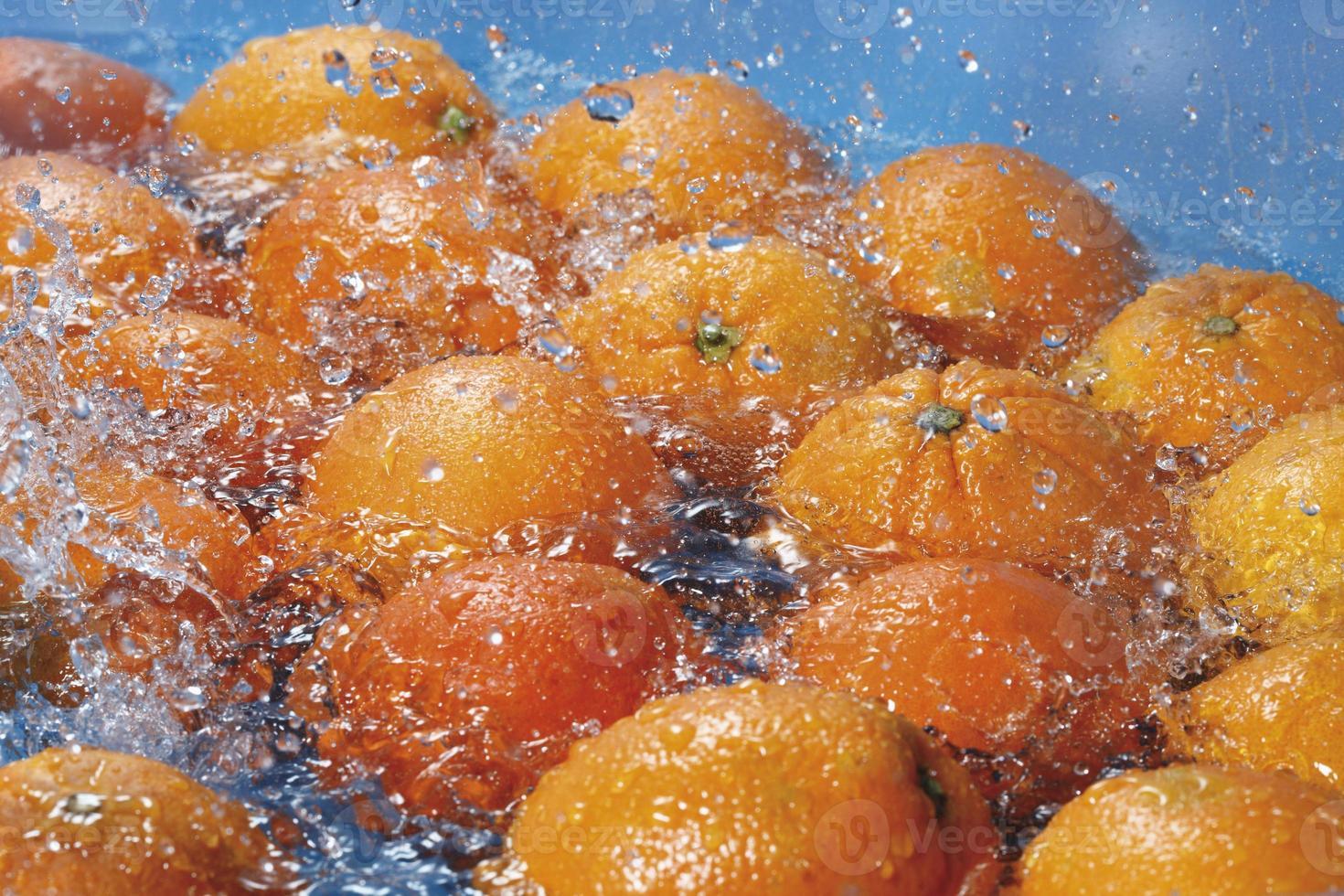 salpicaduras de agua sobre naranjas frescas foto