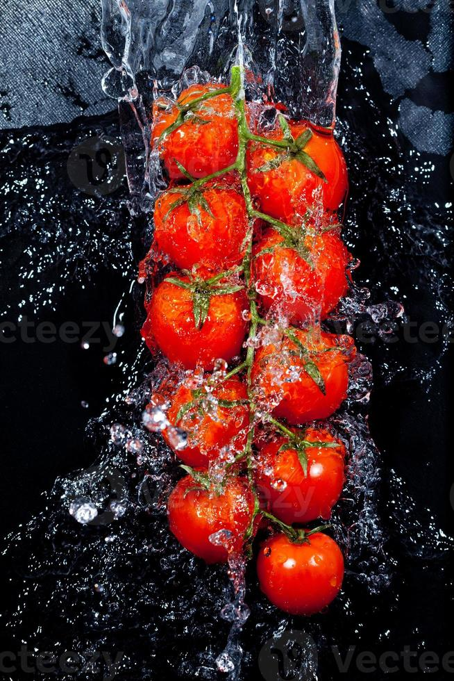 rama de tomates en salpicaduras de agua foto