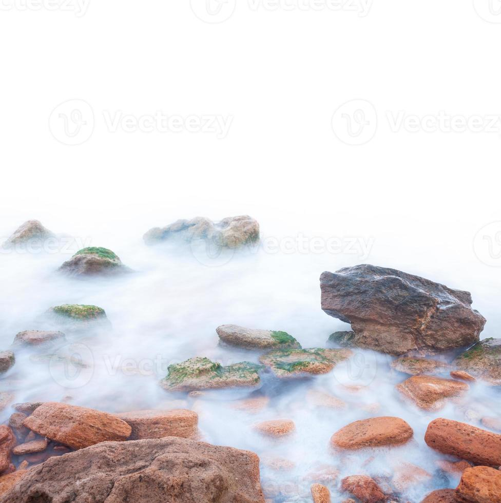 Shore of the sea, rocks and flowing water photo