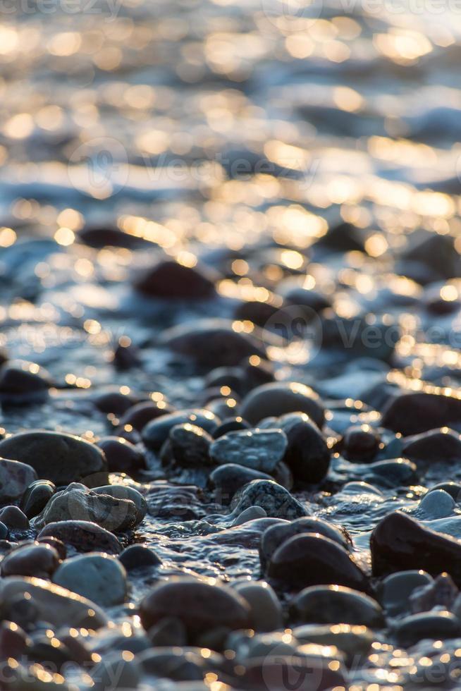 piedras en la playa y el agua de mar foto