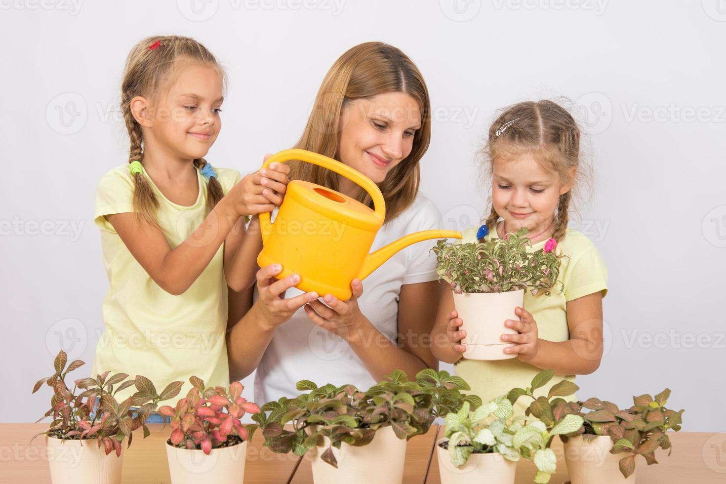 madre e hijos felices regando flores foto