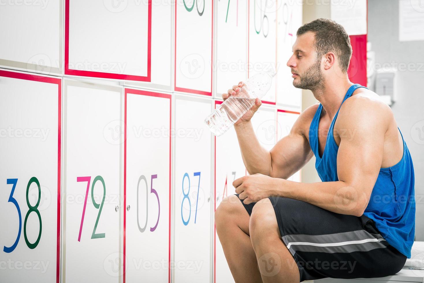 hombre bebiendo agua en el vestuario foto