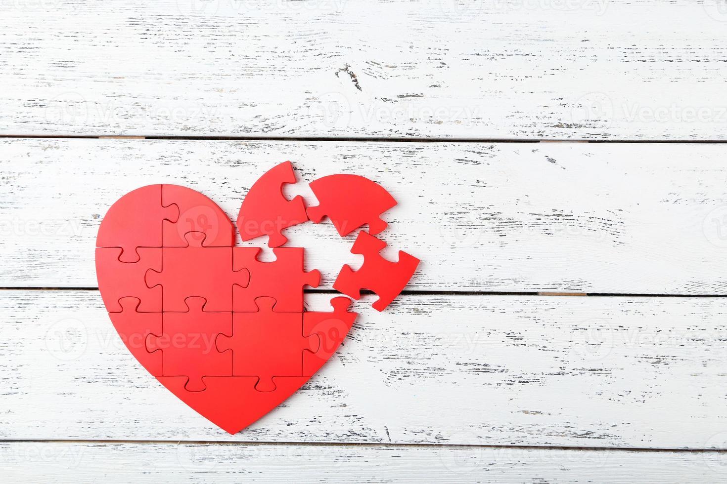 Corazón de rompecabezas rojo sobre fondo blanco de madera foto