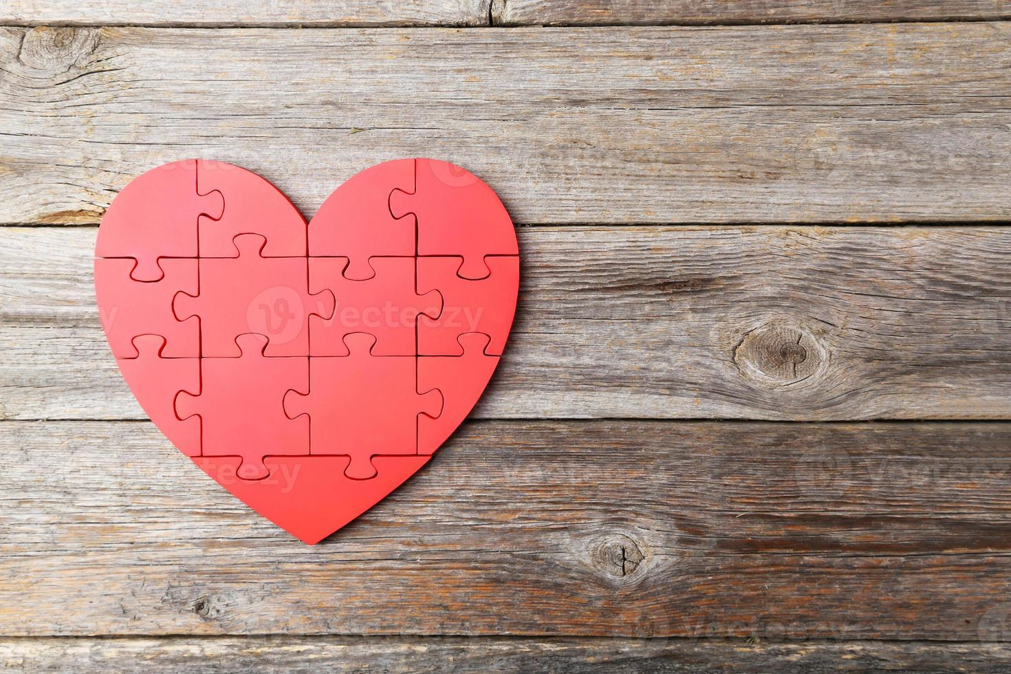 Corazón de rompecabezas rojo sobre fondo de madera gris foto