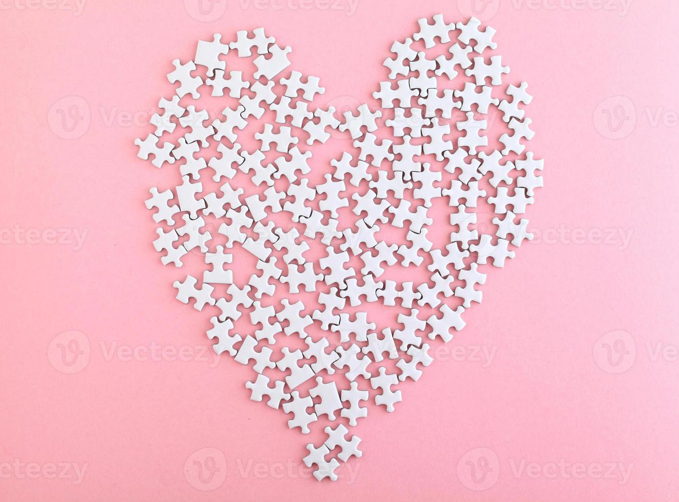 puzzle made heart sharp on pink background photo