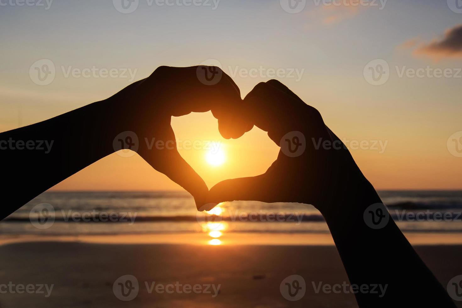 silueta de manos en el símbolo del corazón alrededor del sol foto