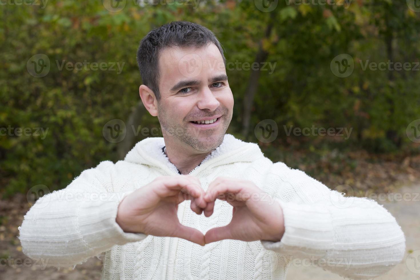 hombre afuera dando forma al corazón con sus manos foto