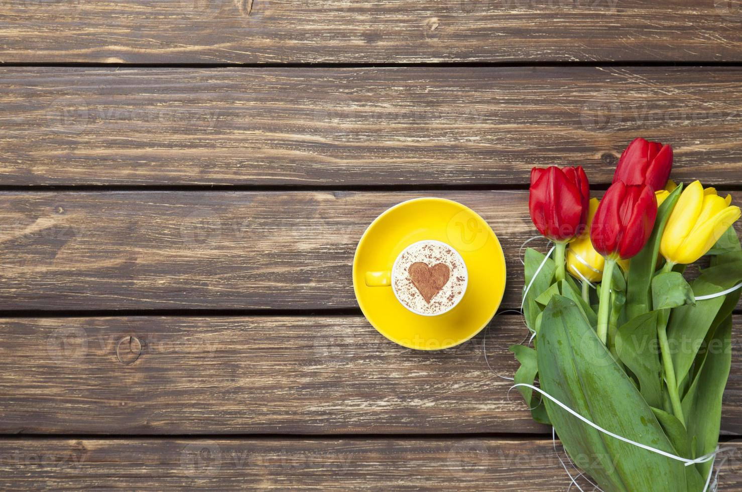 cappuccino with heart shape and bouquet of tulips photo