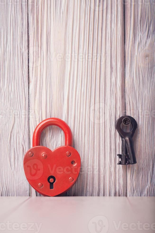 Cerradura y llave en forma de corazón sobre fondo de madera vintage claro foto