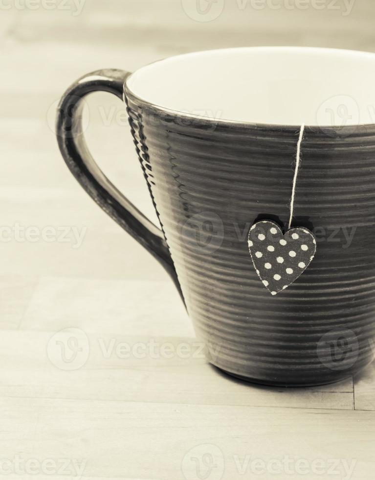 Taza de té en la mesa de madera rústica con etiqueta en forma de corazón foto
