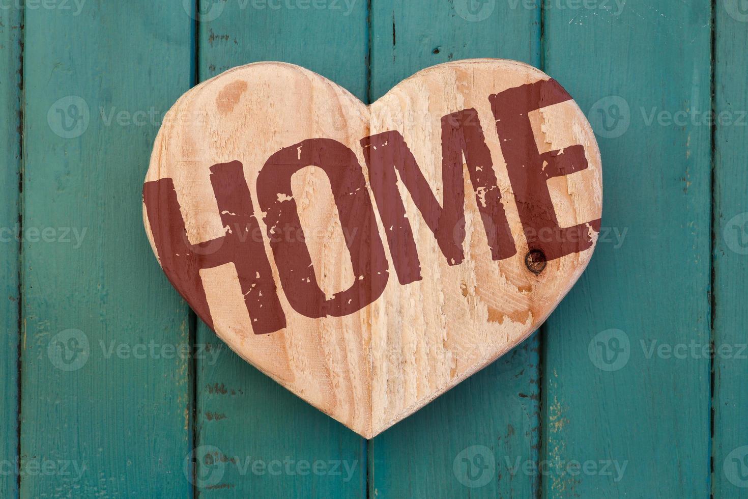 Amor mensagem em casa coração de madeira em fundo pintado de turquesa foto