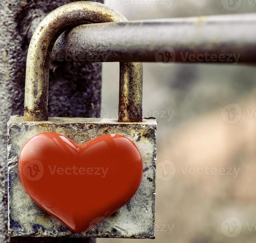 Candado en forma de corazón bloqueado oxidado envejecido sobre baranda metálica foto