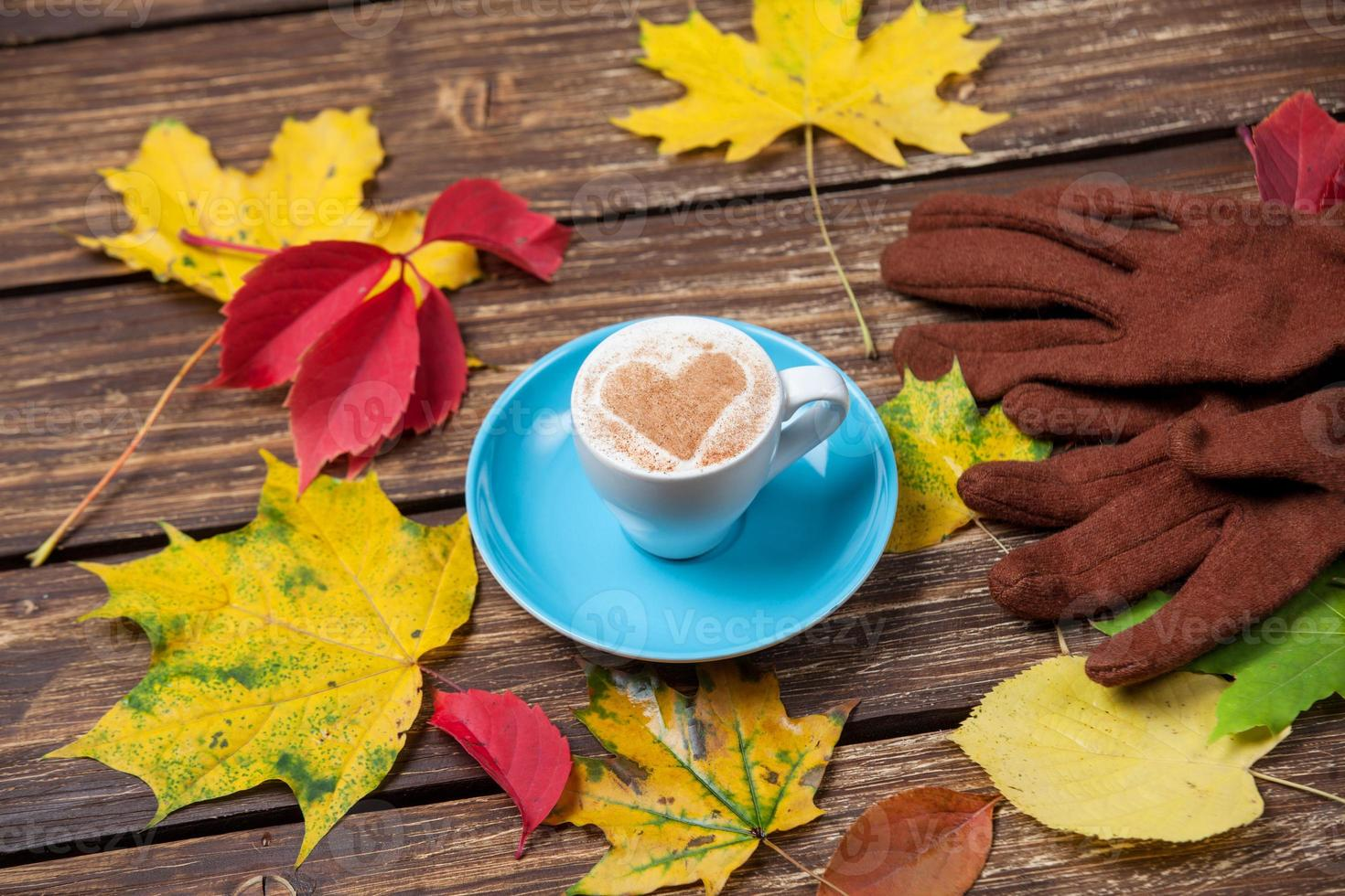Autumn leafs,gloves and coffee cup on wooden table. photo