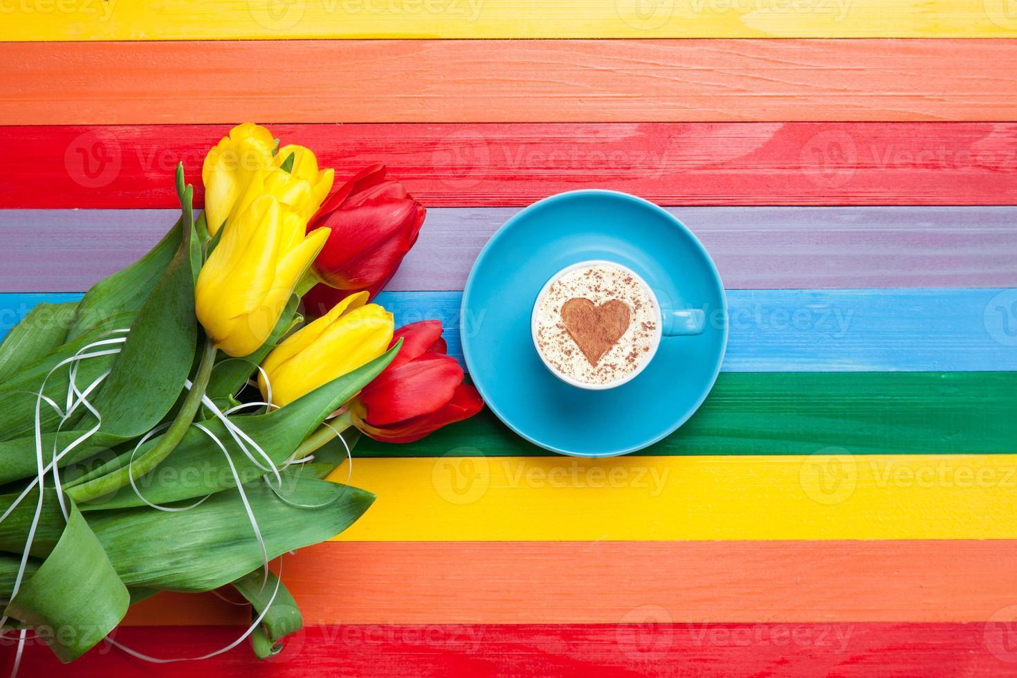 taza de capuchino con forma de corazón y ramo de tulipanes foto