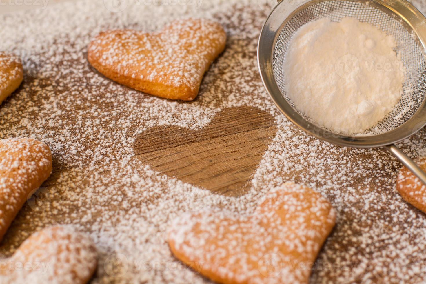 Polvo de galletas en forma de corazón con azúcar, una silueta, colador foto