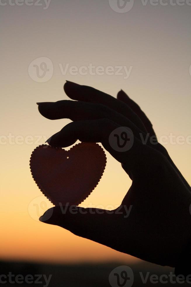 Holding an heart shape silhouette photo