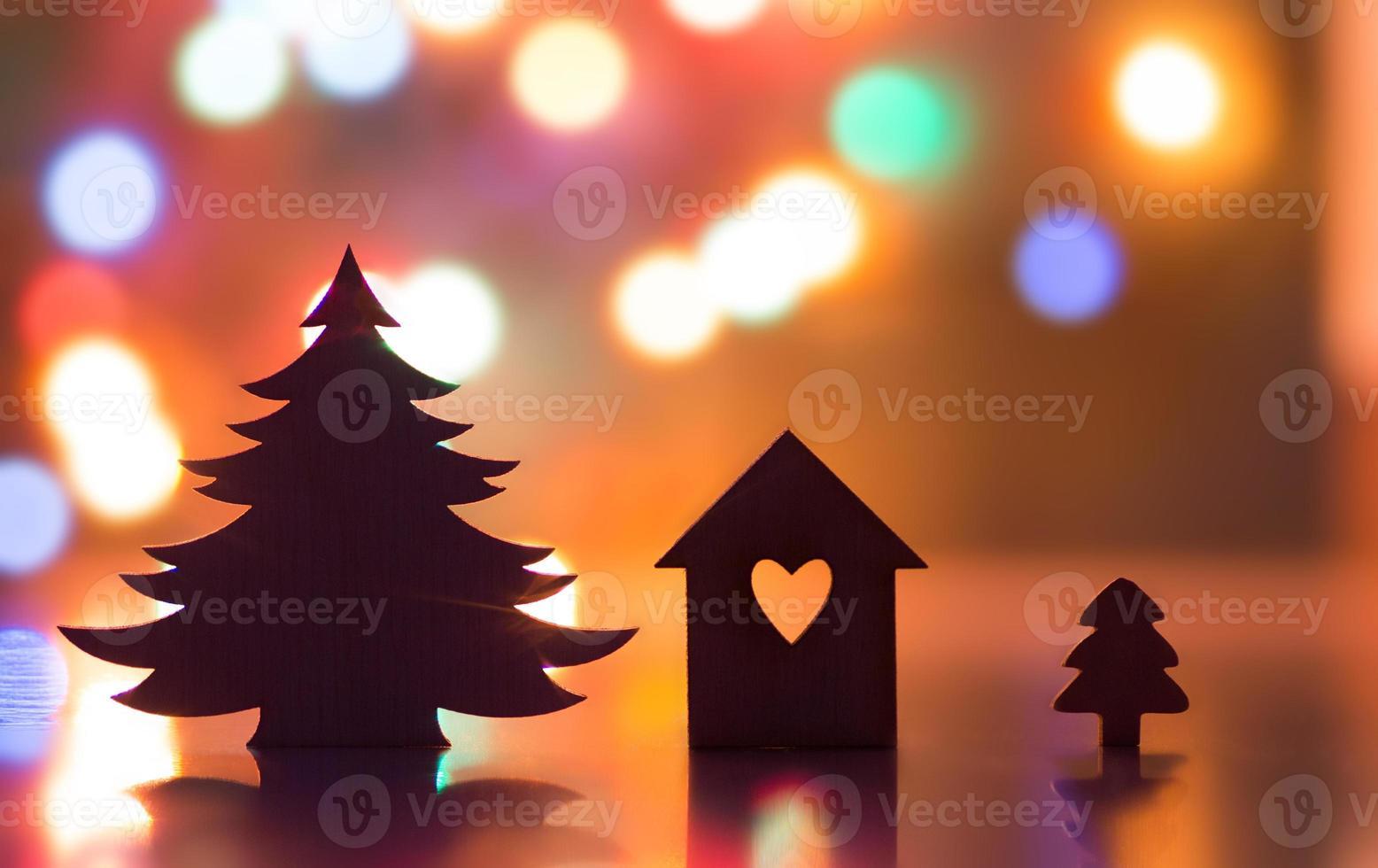 silueta de casa con agujero en forma de corazón y árbol de navidad foto