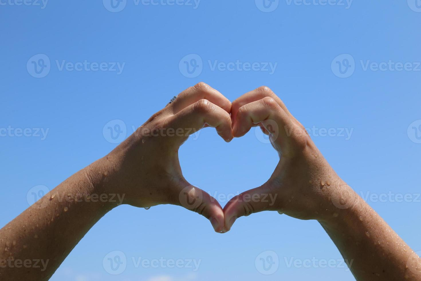 Heart symbol made with hands photo