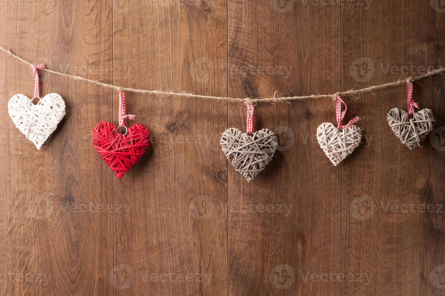 Hearts hanging on wooden wall photo