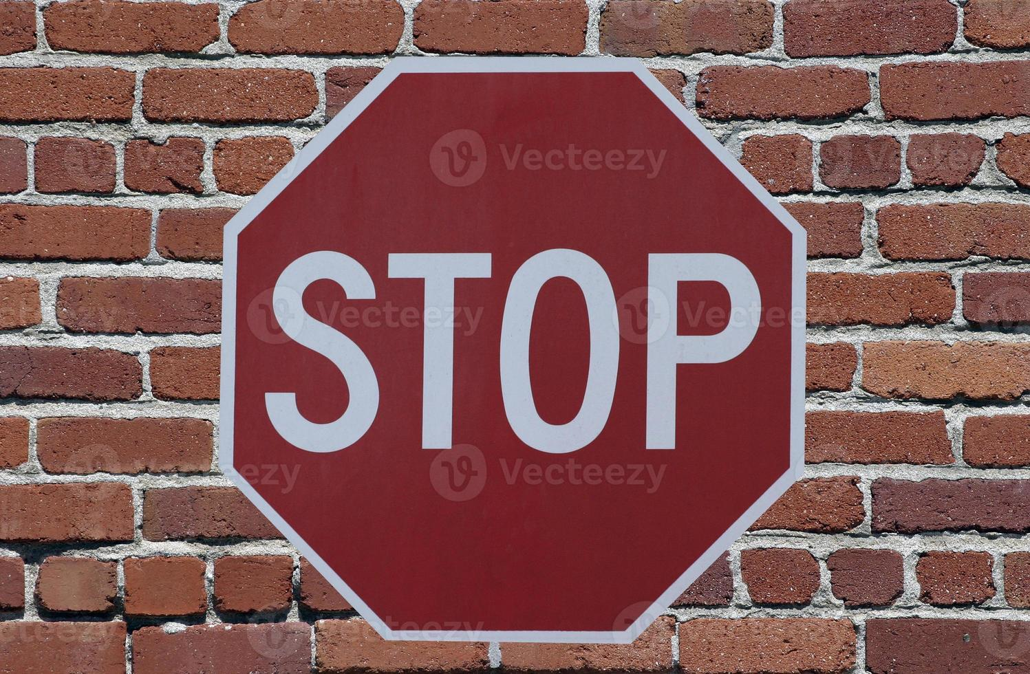Stop Sign against brick wall photo