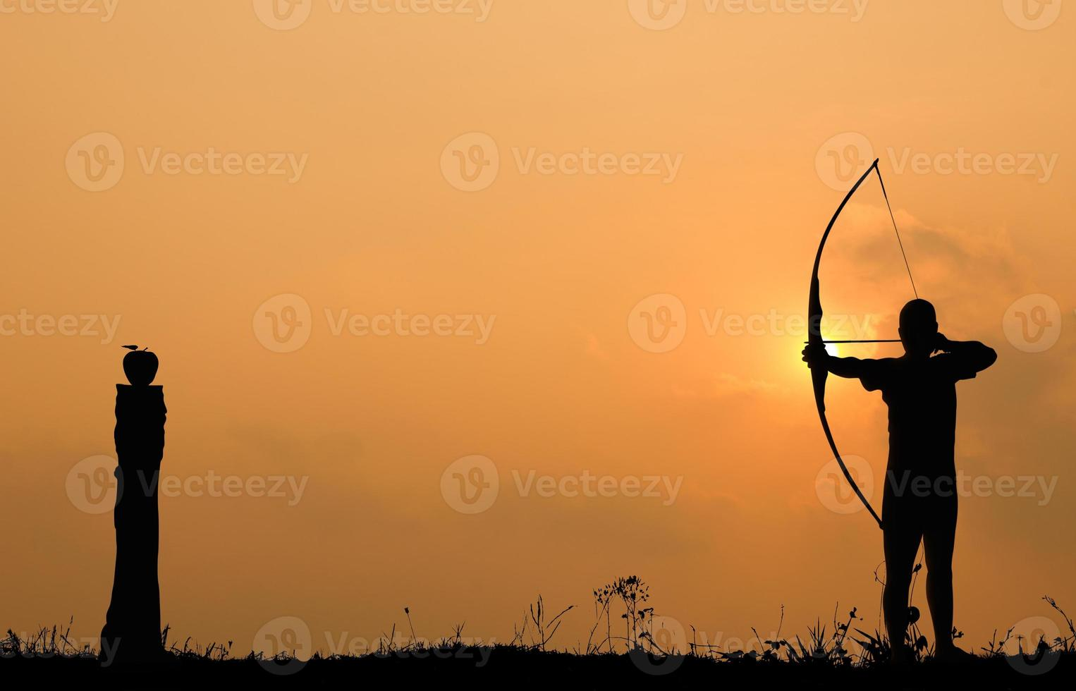 Silhouette archery shoots a bow at an apple on timber photo