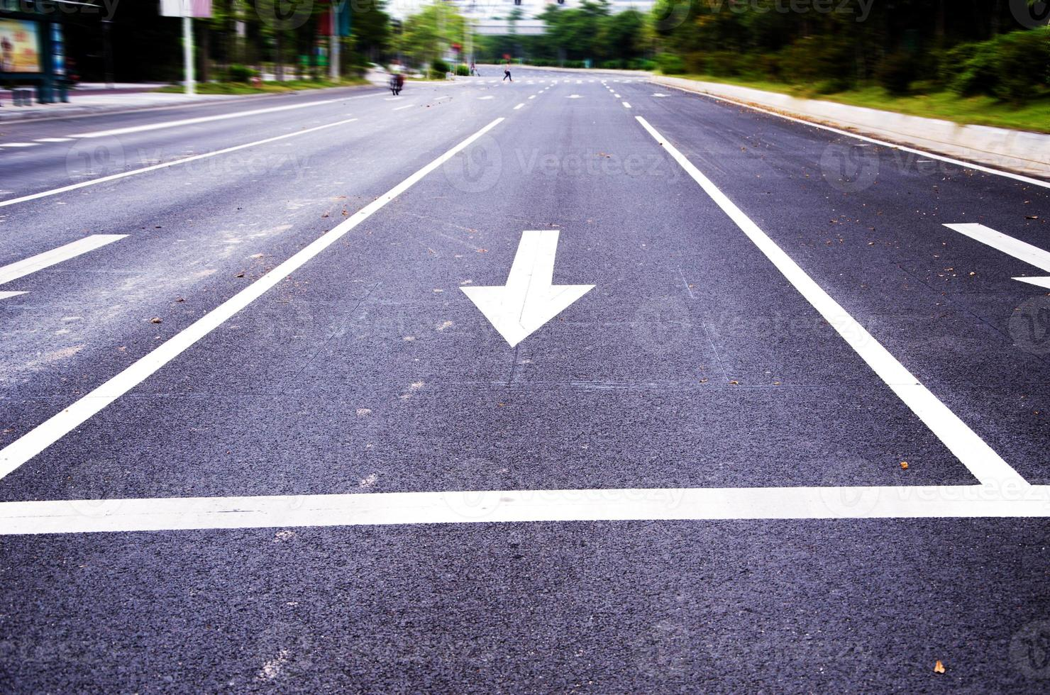 white painted arrow on black asphalt road photo