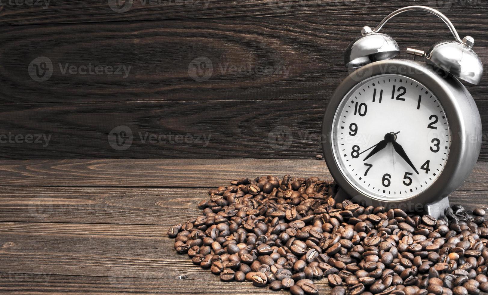 Despertador con campanas y granos de café derramados. foto