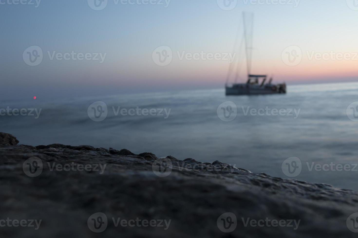 Yacht at sea after sunset photo