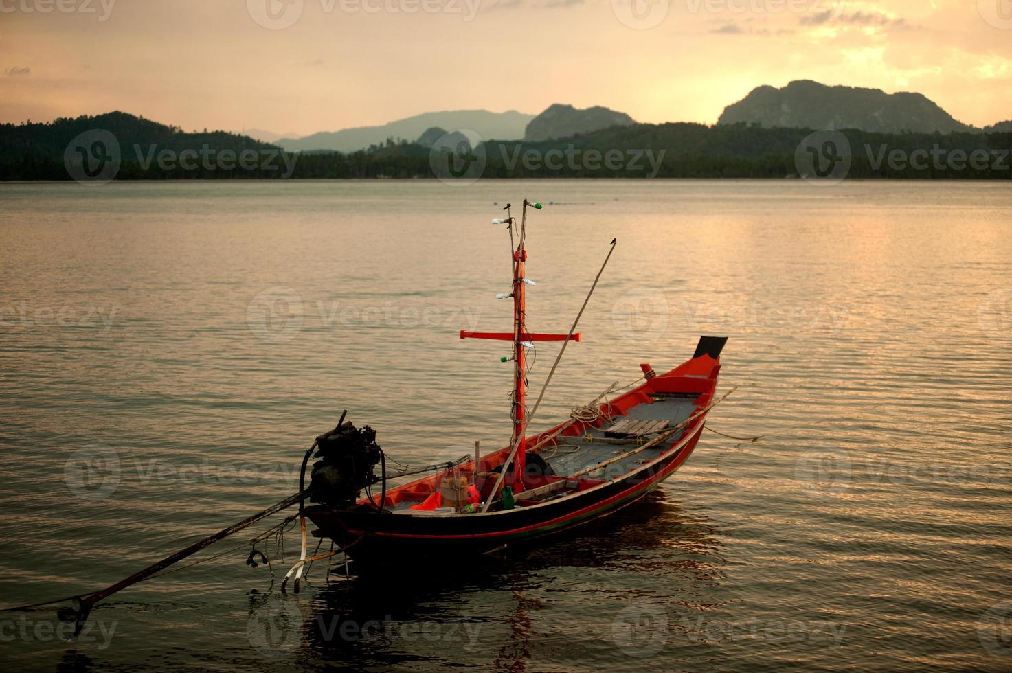 Sunset scenic view of traditional fishing long tailed boat. photo