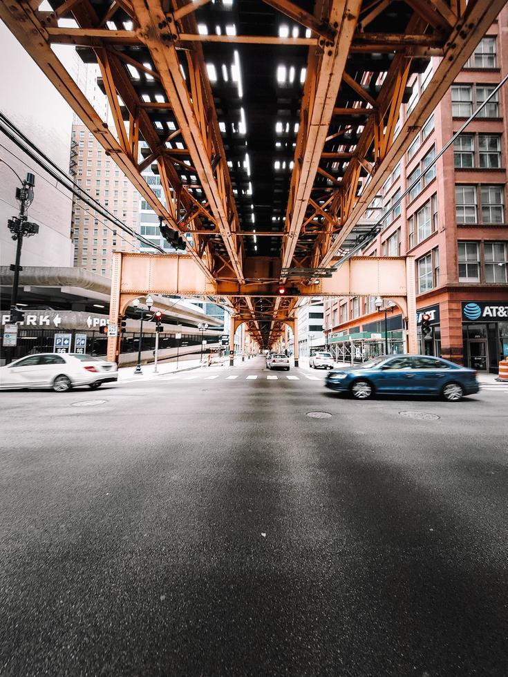 Cars speeding by under a brown metal bridge photo
